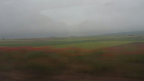 Photo taken from a train of the rain in Spain falling mainly on the plain.