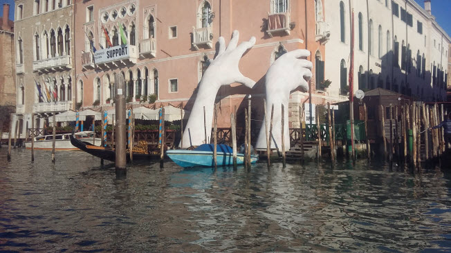 "Lorenzo Quinn's ""Suppport"" sculpture rising out of the waters of the Grand Canal in Venice."