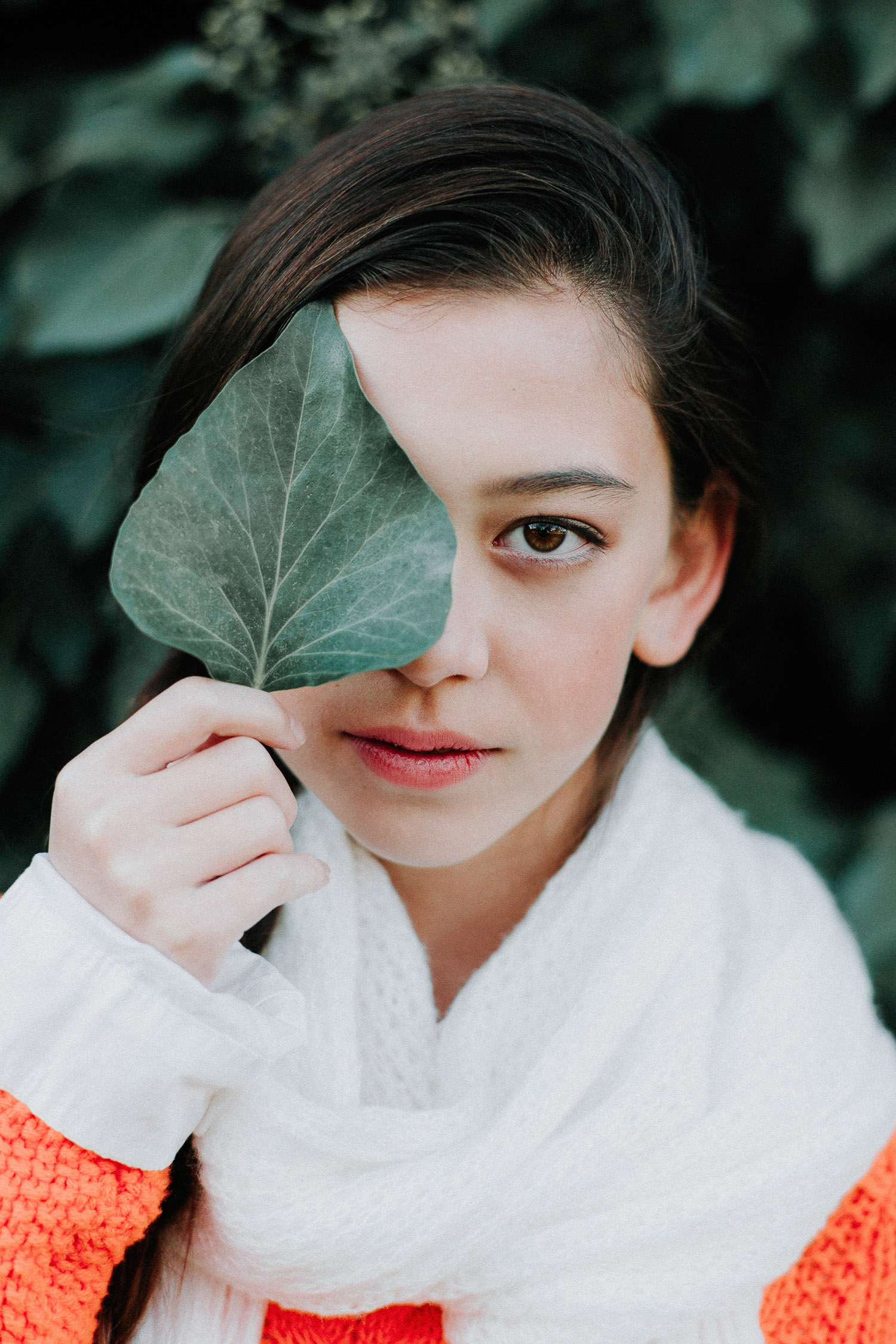 Image of orange sweater girl over her one eye with a leaf