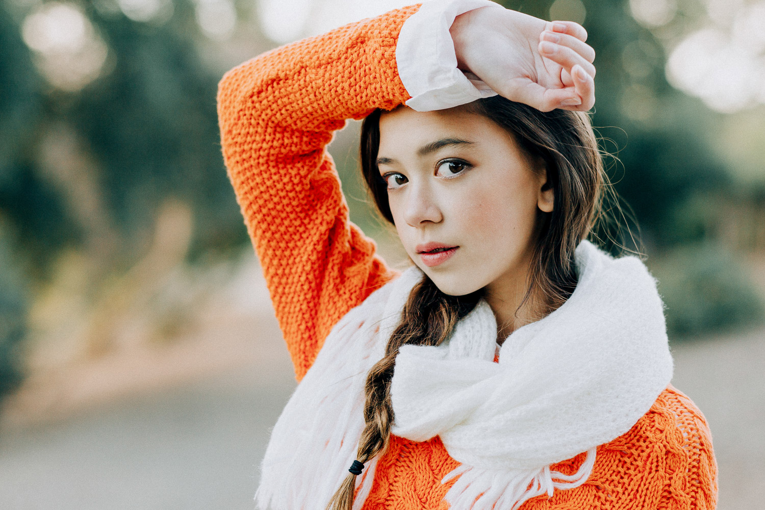 Image of an orange sweater girl puts her arm on her forehead