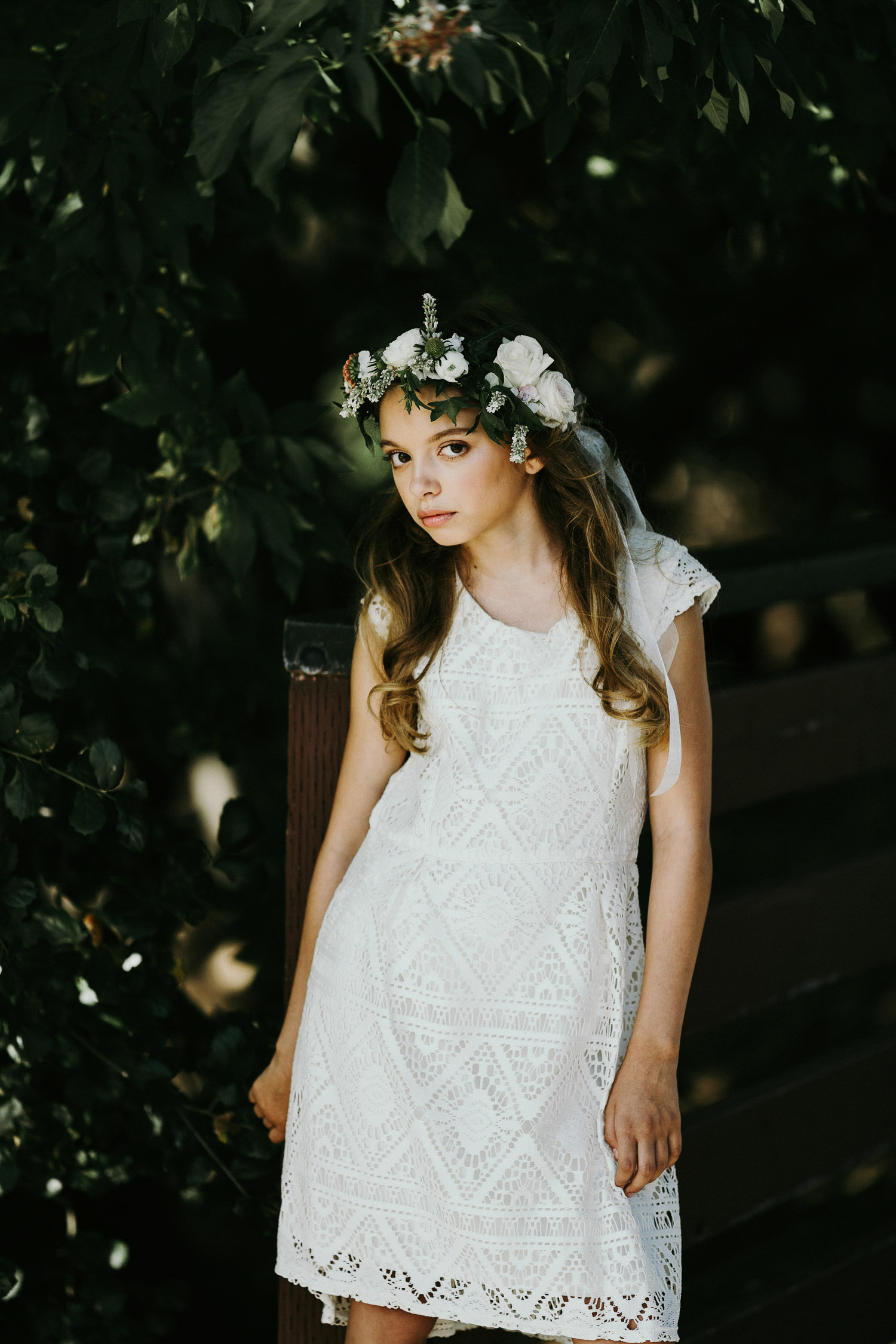 Image of a white dress girl standing in the tree shadow