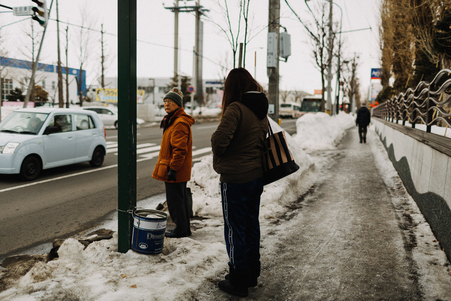 Image of two people waiting for bus