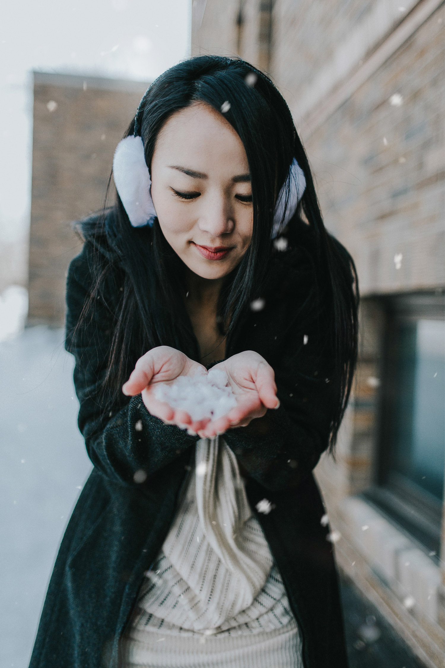 Image of a girl looks at the snow in her hands