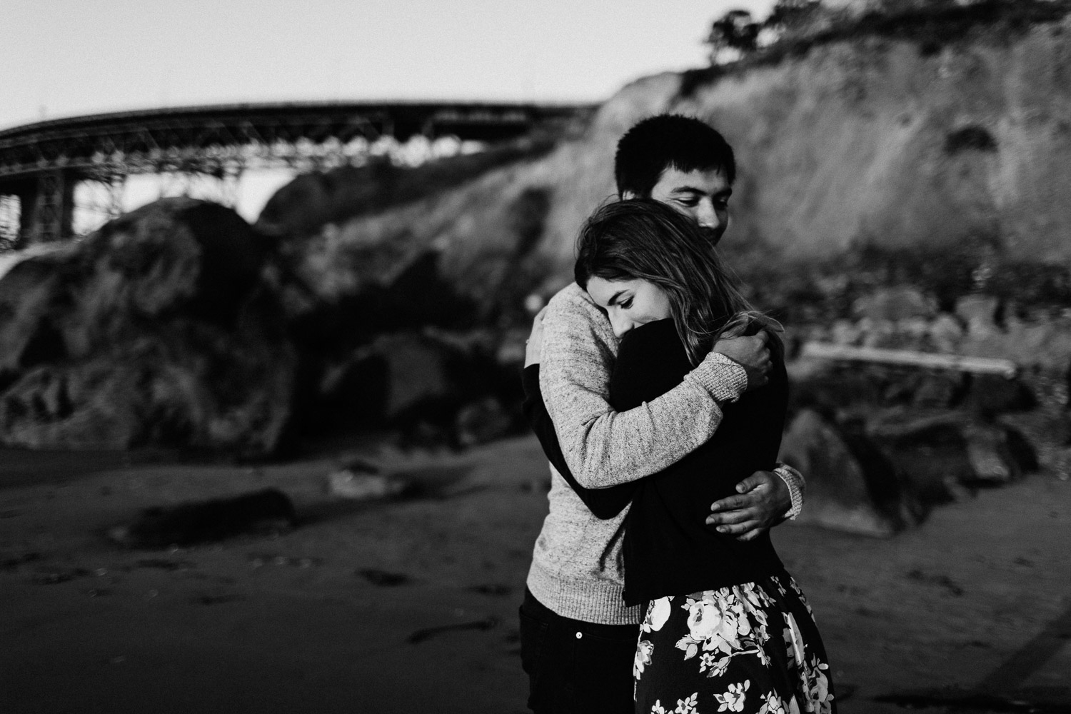 Black and White image of couple hug each other in front of Golden Gate Bridge