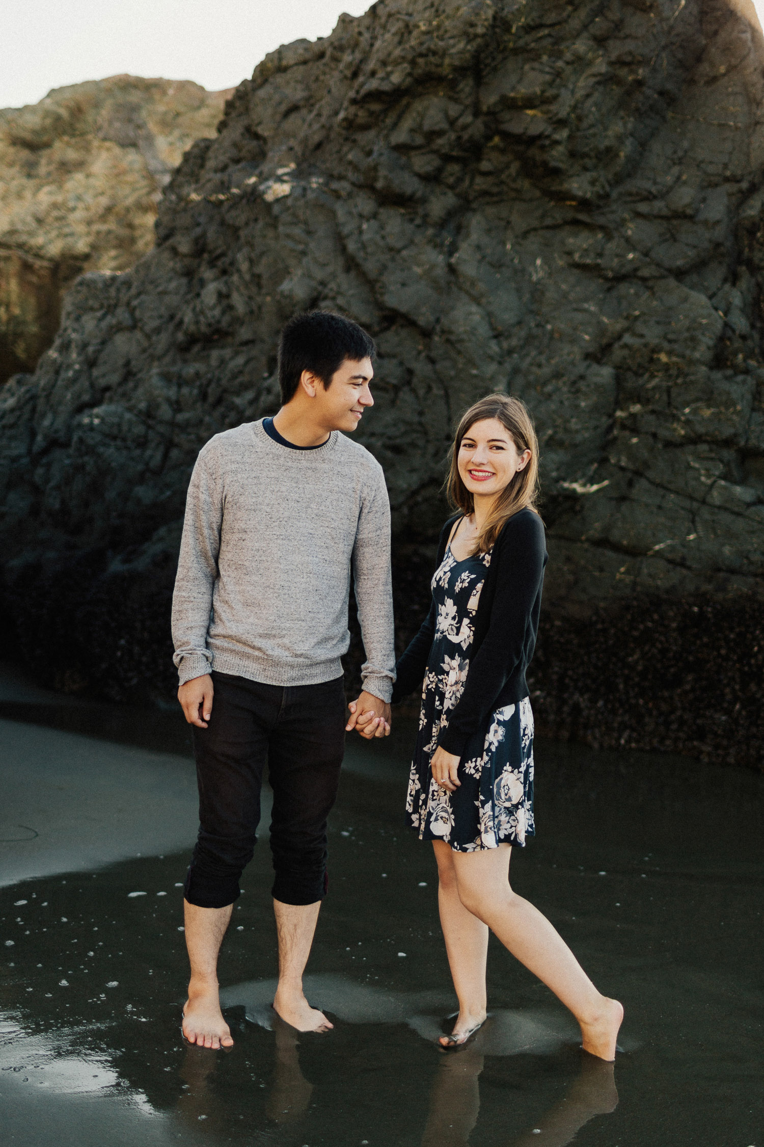 Image of couple hold hands together smiling on beach