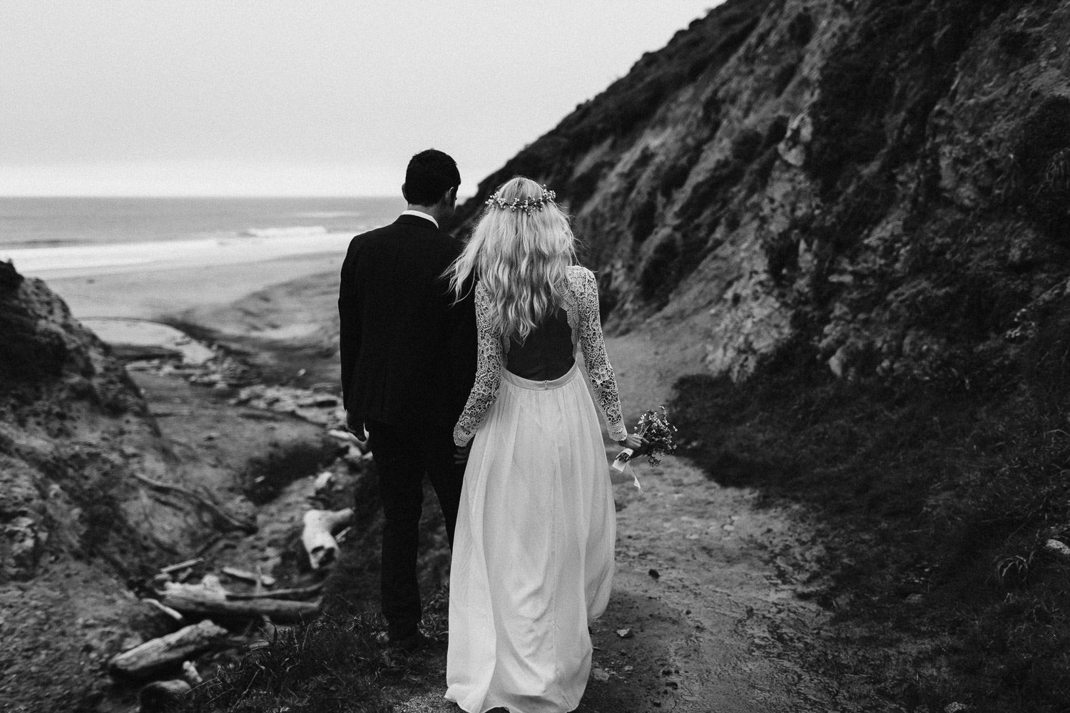 Black and White image of bride and groom walk together