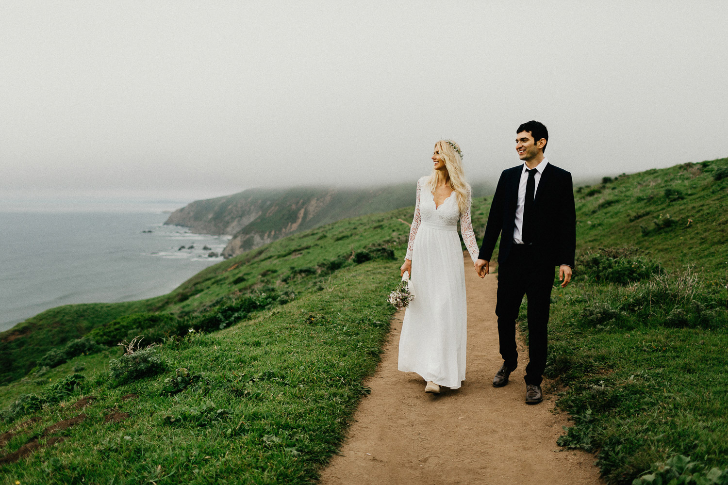 Image of groom holds hand with bride on top of mountain