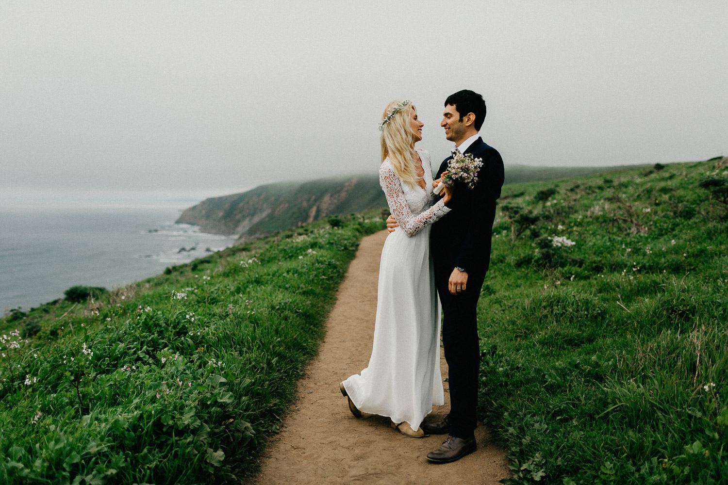 Image of groom holds bride from the front