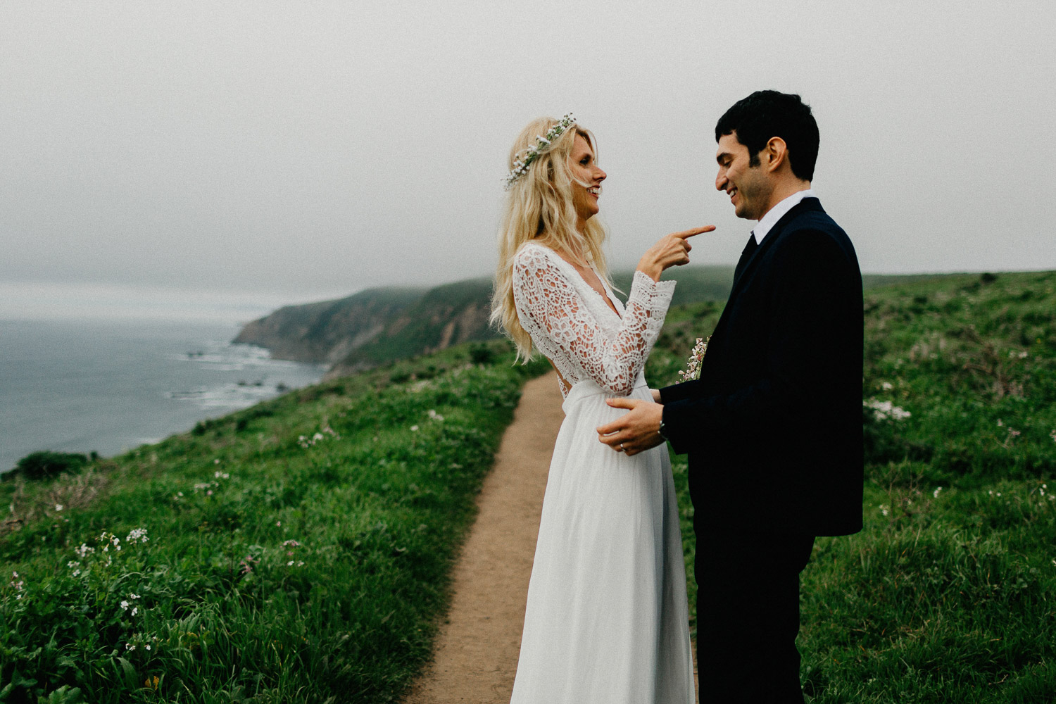 Image of bride points to groom and smiles