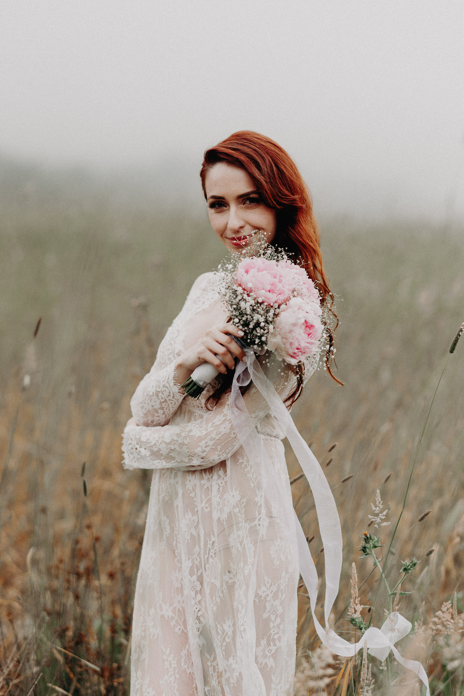 Image of red hair bride holds pink bouquet and smiles