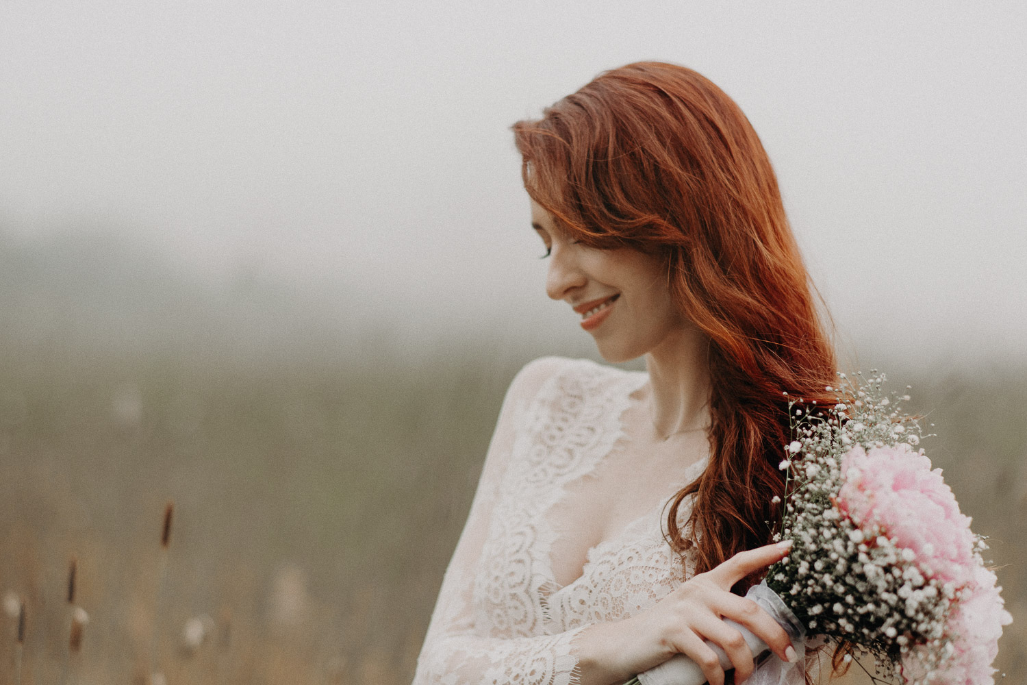 Image of red hair bride holds pin bouquet and smiles