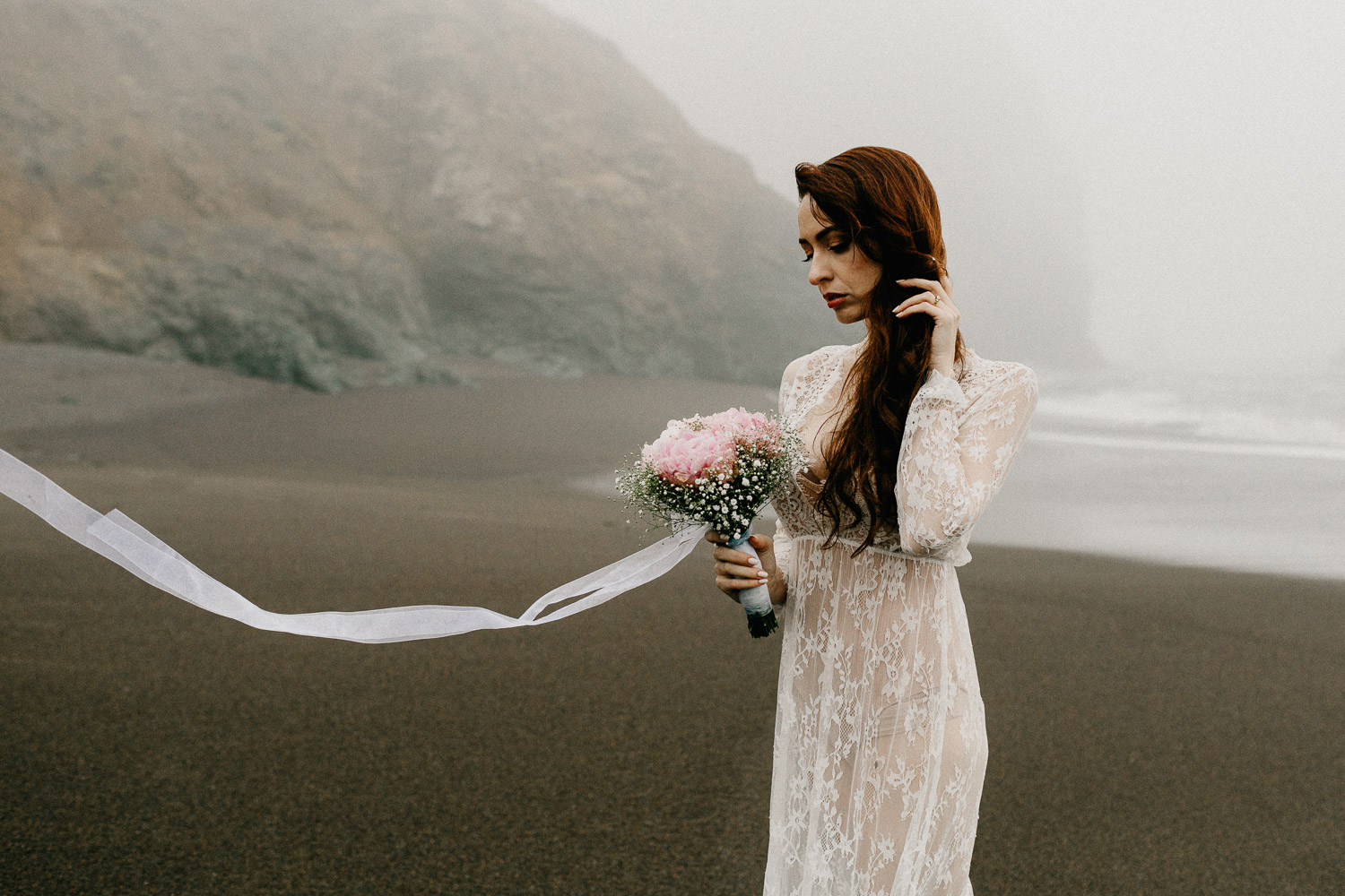 Image of red hair bride holds pink bouquet standing on beach