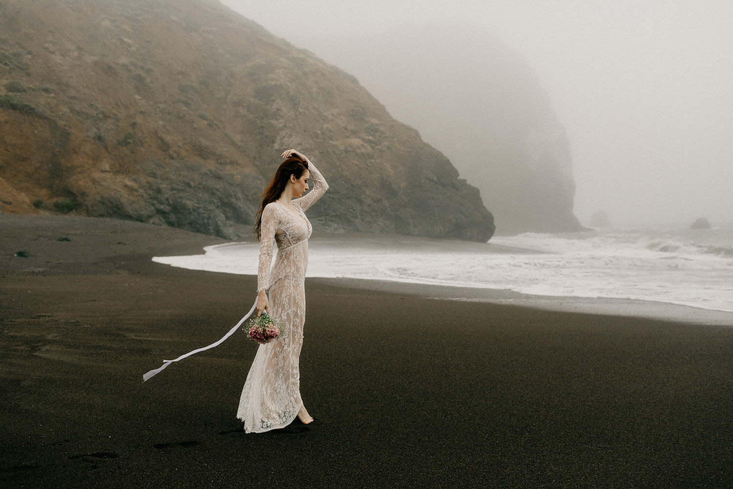 Image of red hair bride holds bouquet standing on beach