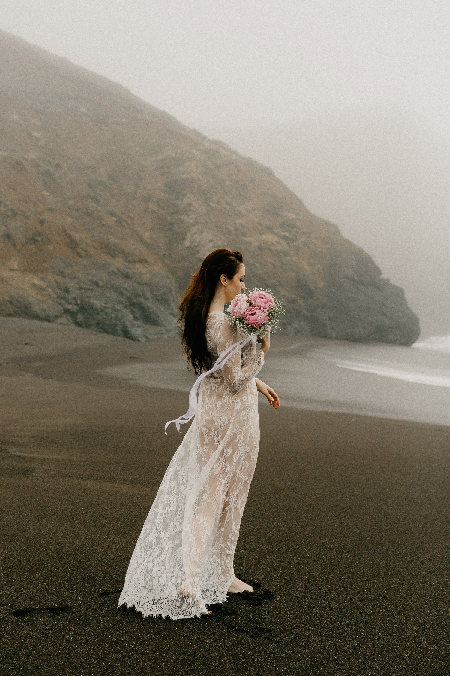 Image of red hair bride holds pink bouquet walk on beach