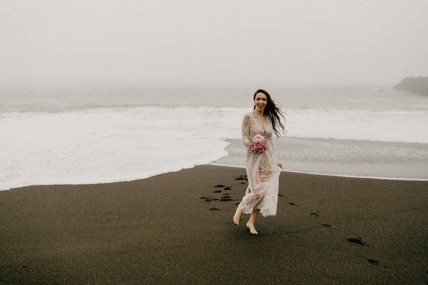 Image of red hair bride holds pink bouquet smiles on beach