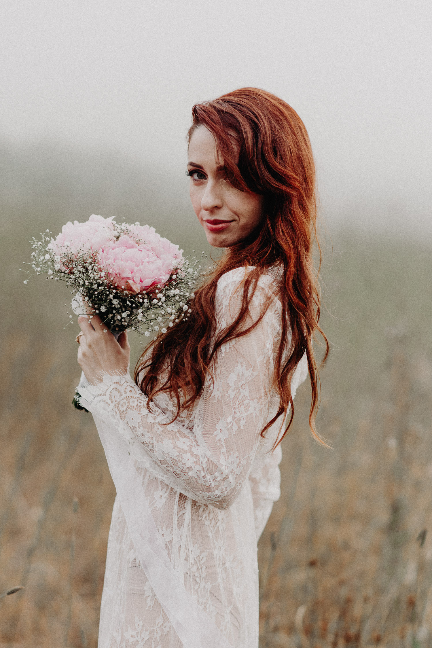 Image of red hair bride holds pink bouquet looks at the camera