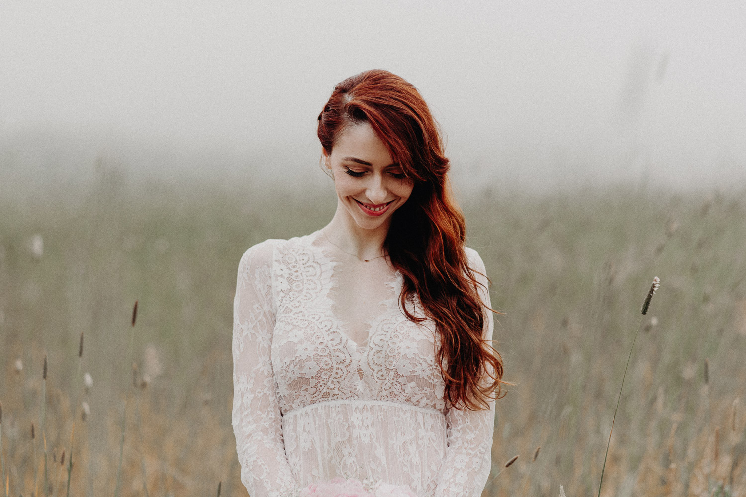 Image of red hair bride looks down and smiles