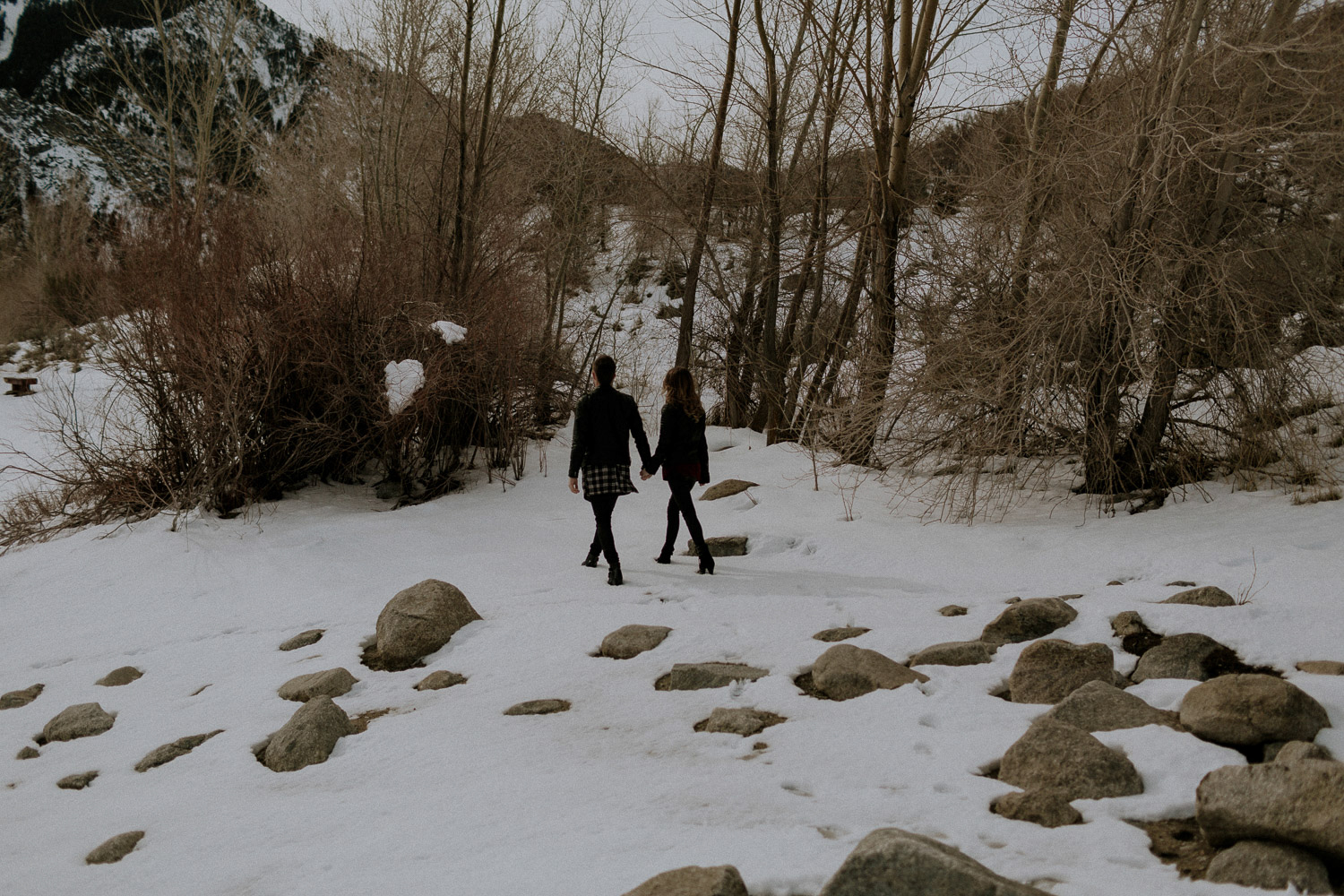 Image of couple hold hands together and walk in snow