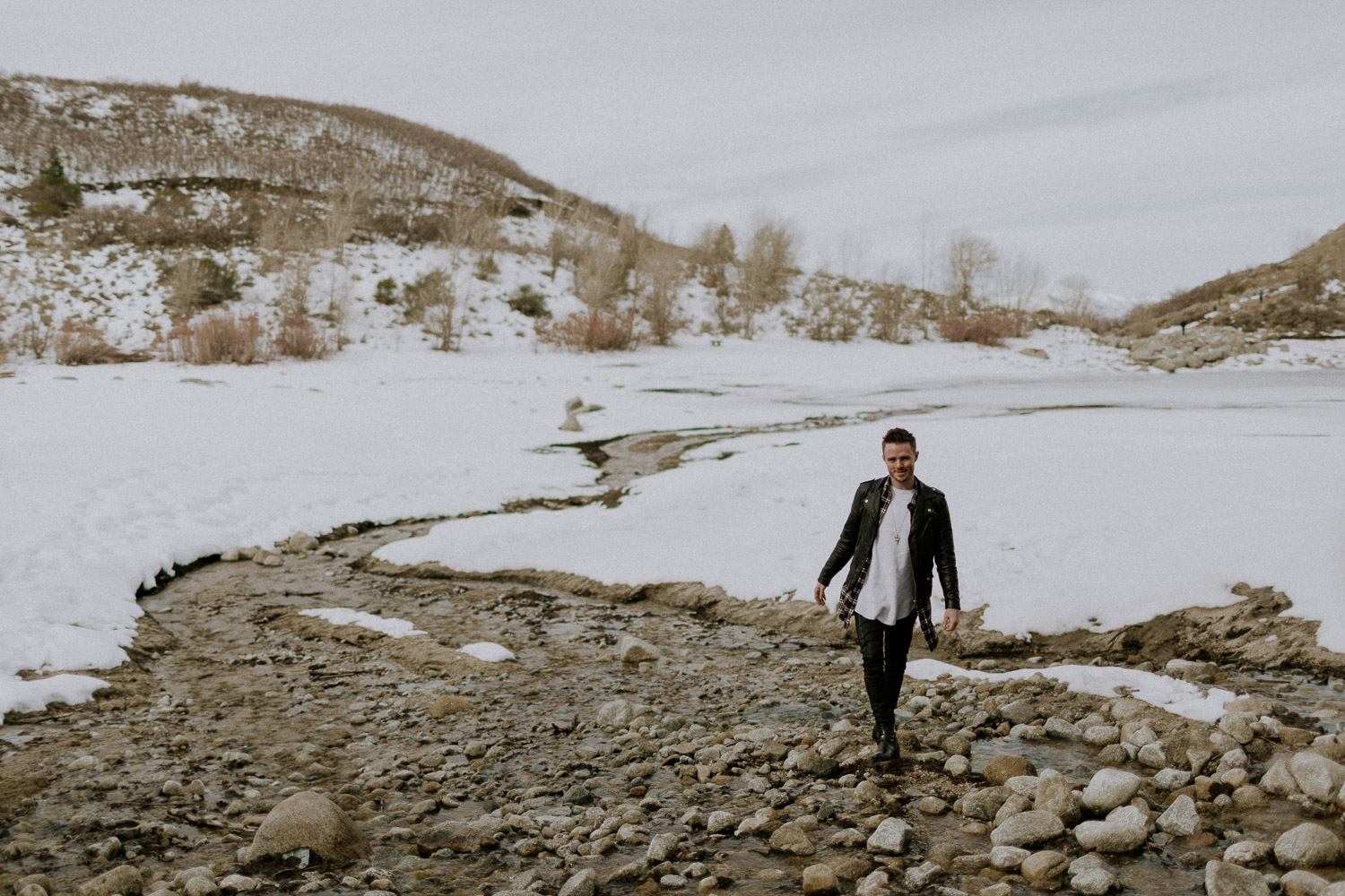 Image of a guy stand in front of yellow hills and white snow