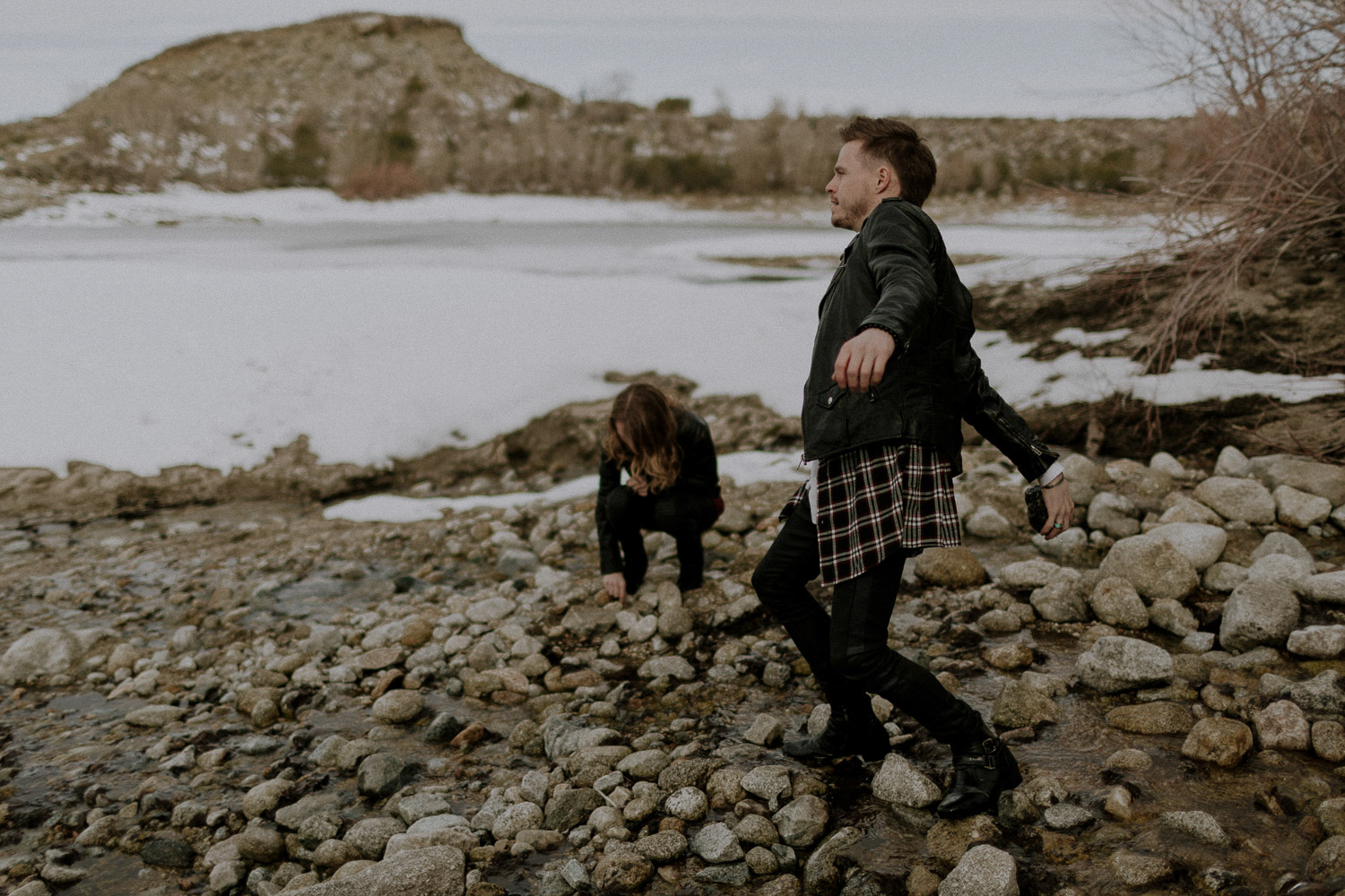 Image of couple pick up rocks to throw