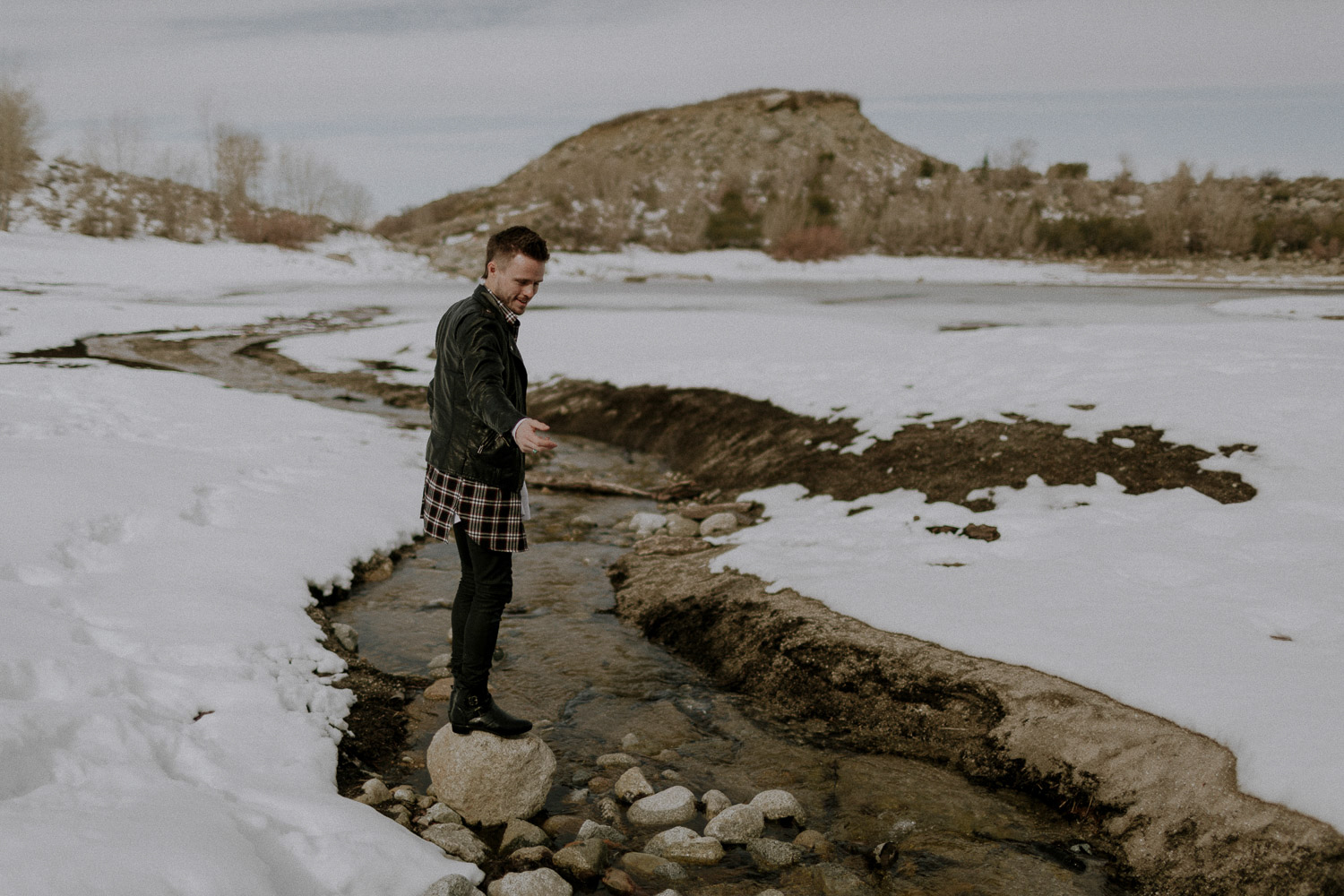 Image of guy stands on rock between snow