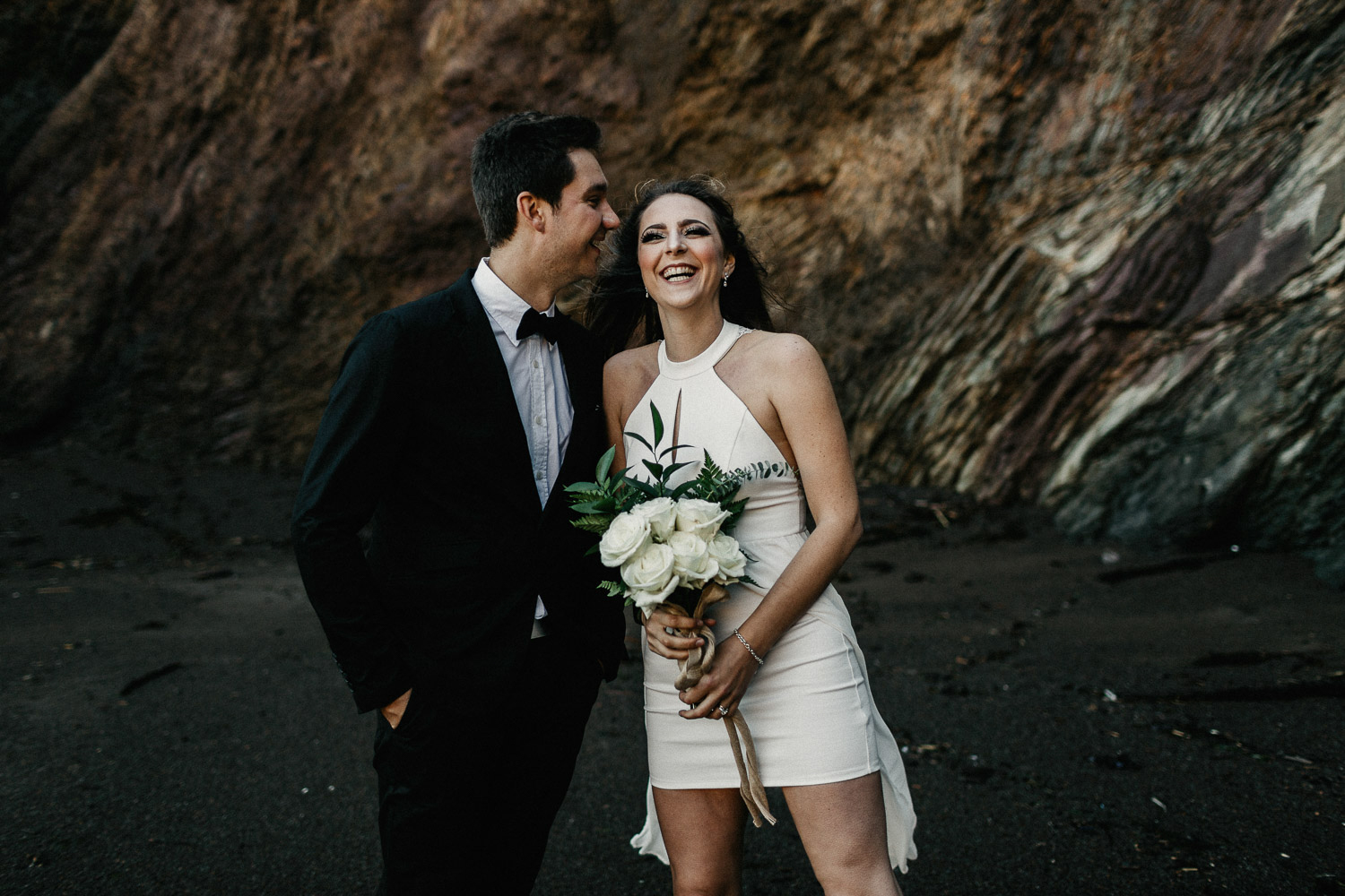 Image of bride and groom laugh together on beach