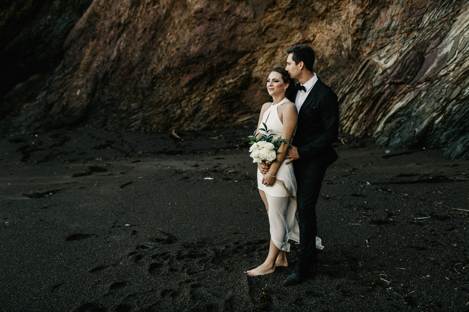 Image of groom and bride stand together on beach