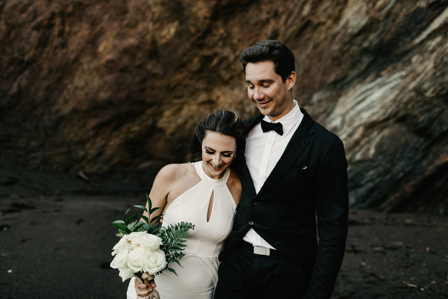 Image of groom holds bride and smiles together on beach
