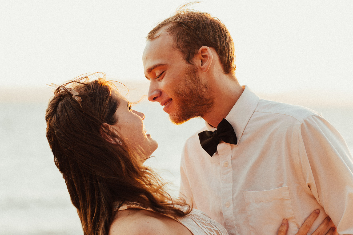 Image of groom looks at bride in the sunset
