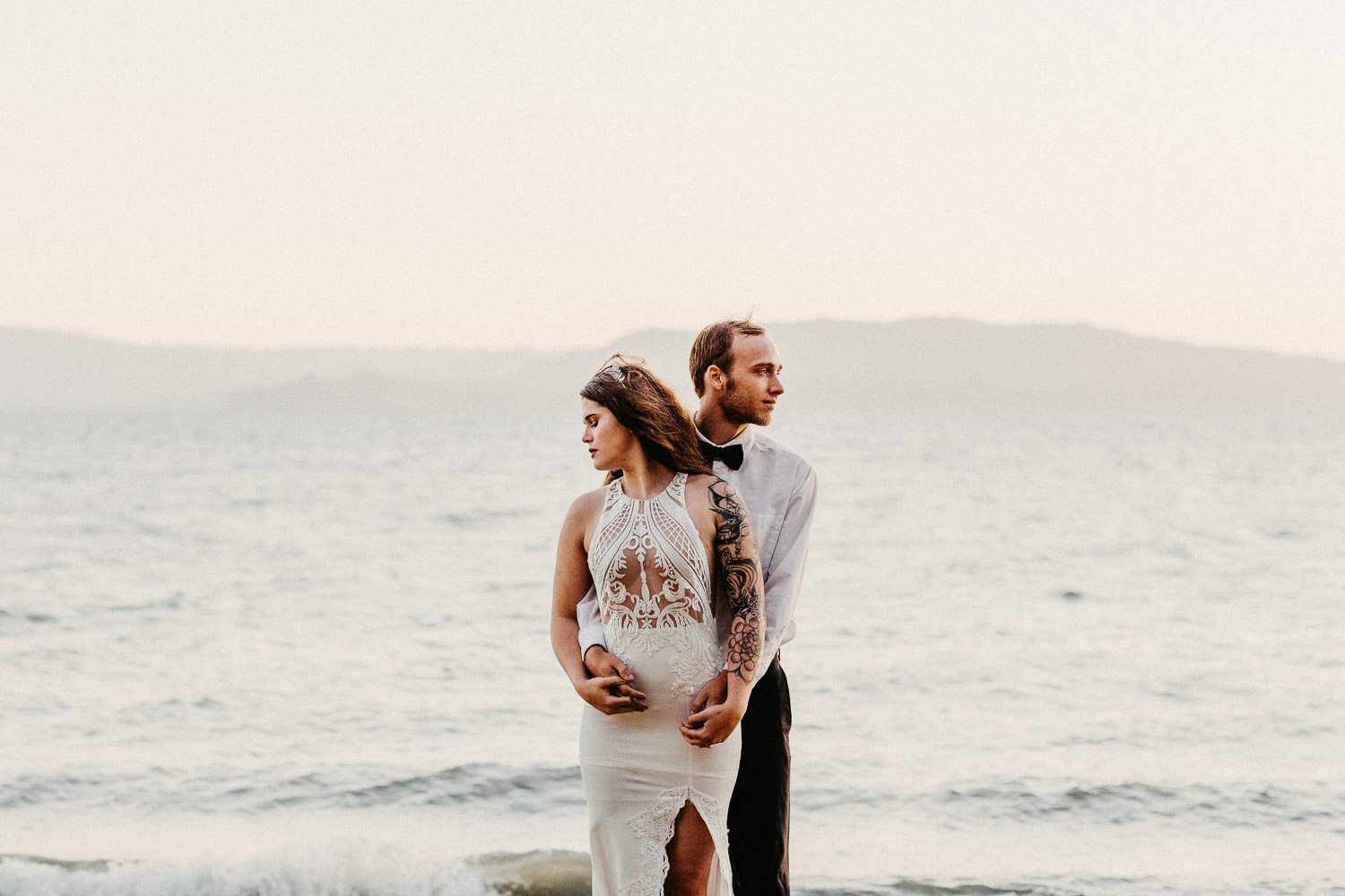 Image of groom holds bride next to water