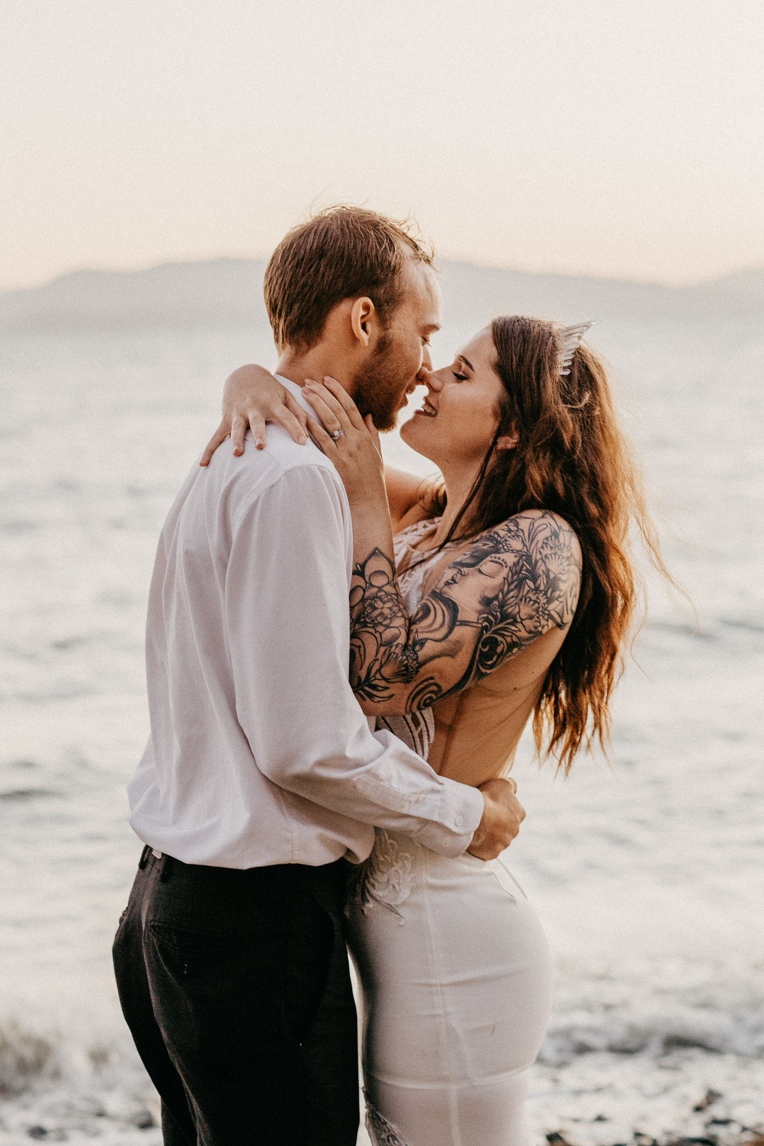 Image of groom holds bride and smile together next to water
