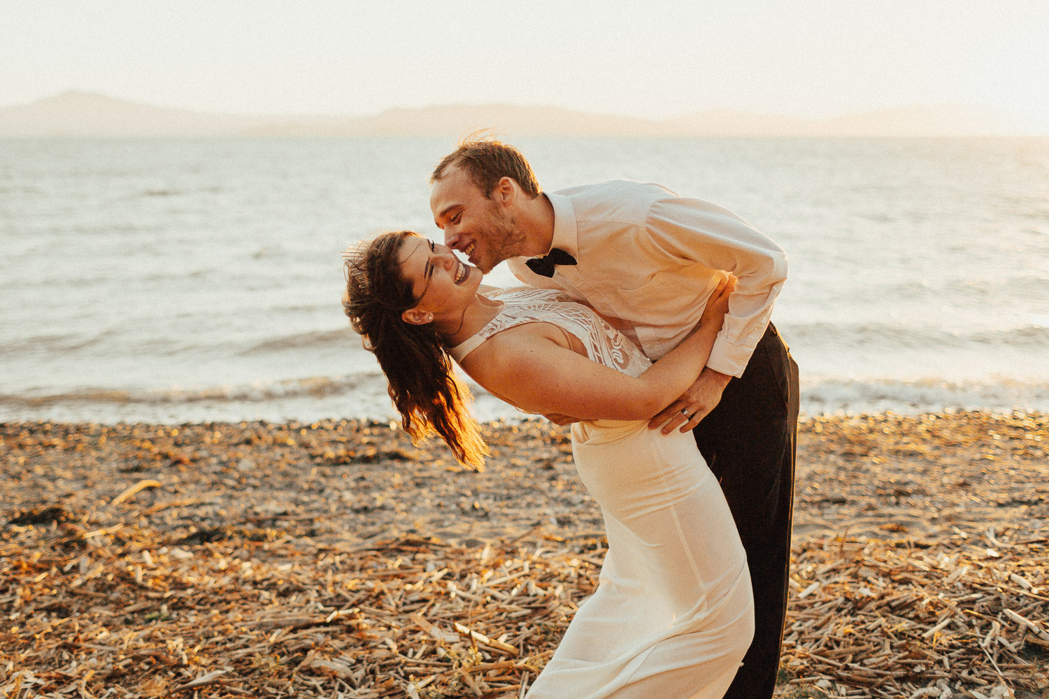 Image of groom tries to kiss bride next to water