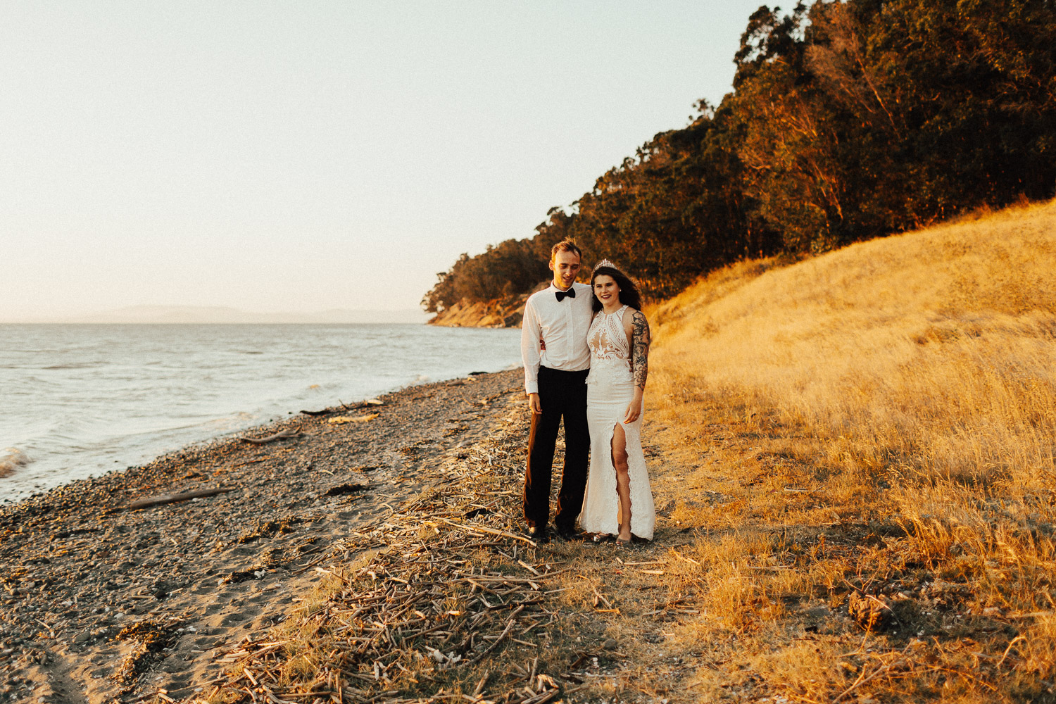 Image of groom and bride stand next to each other next to water