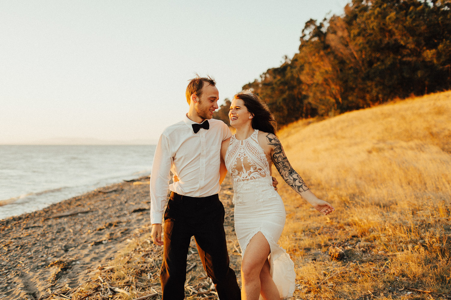 Image of groom and bride walk together on the beach