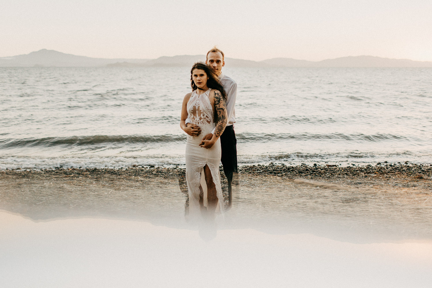 Image of groom holds bride from the back on the beach