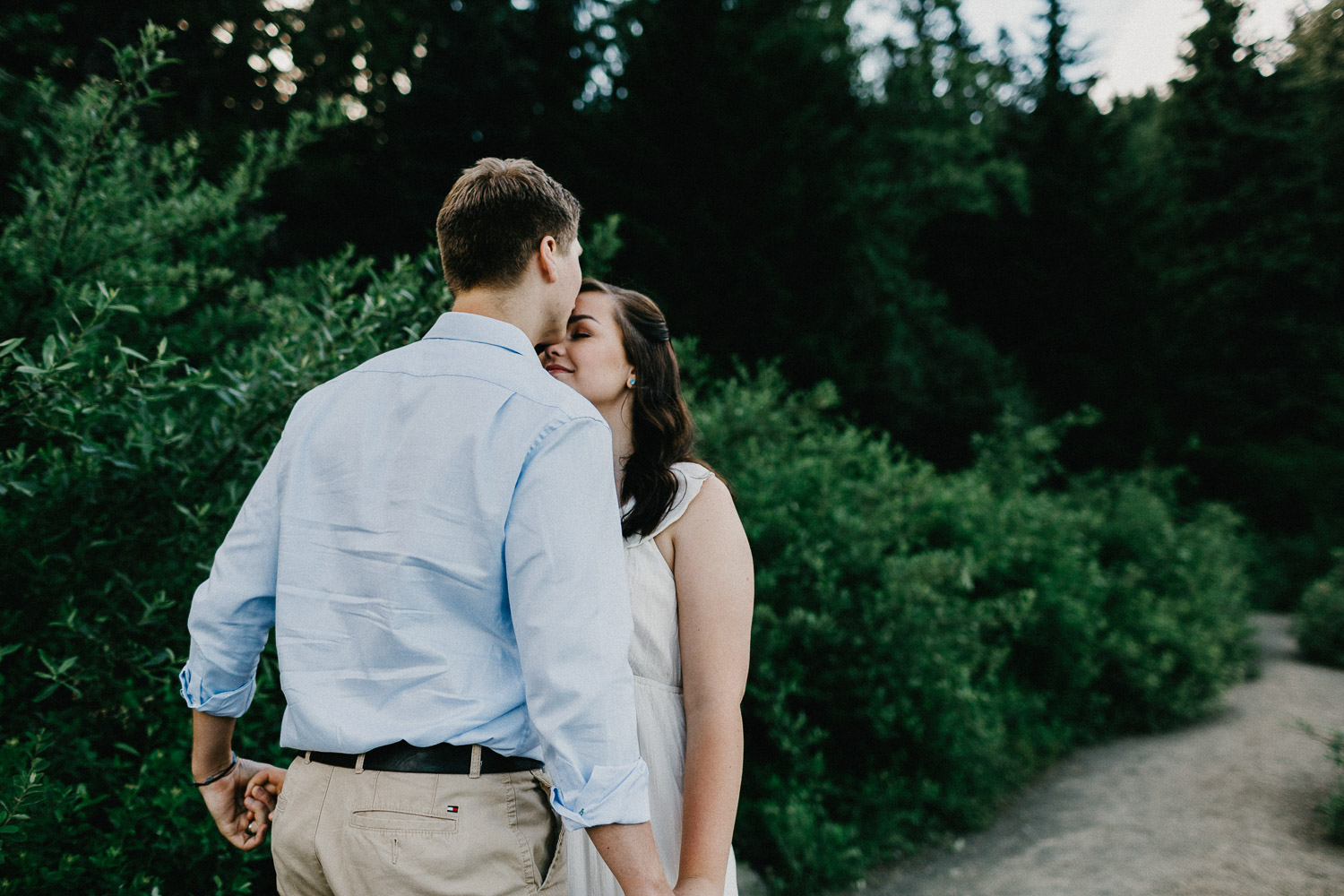 Image of the guy kisses the girl in front of green pine trees
