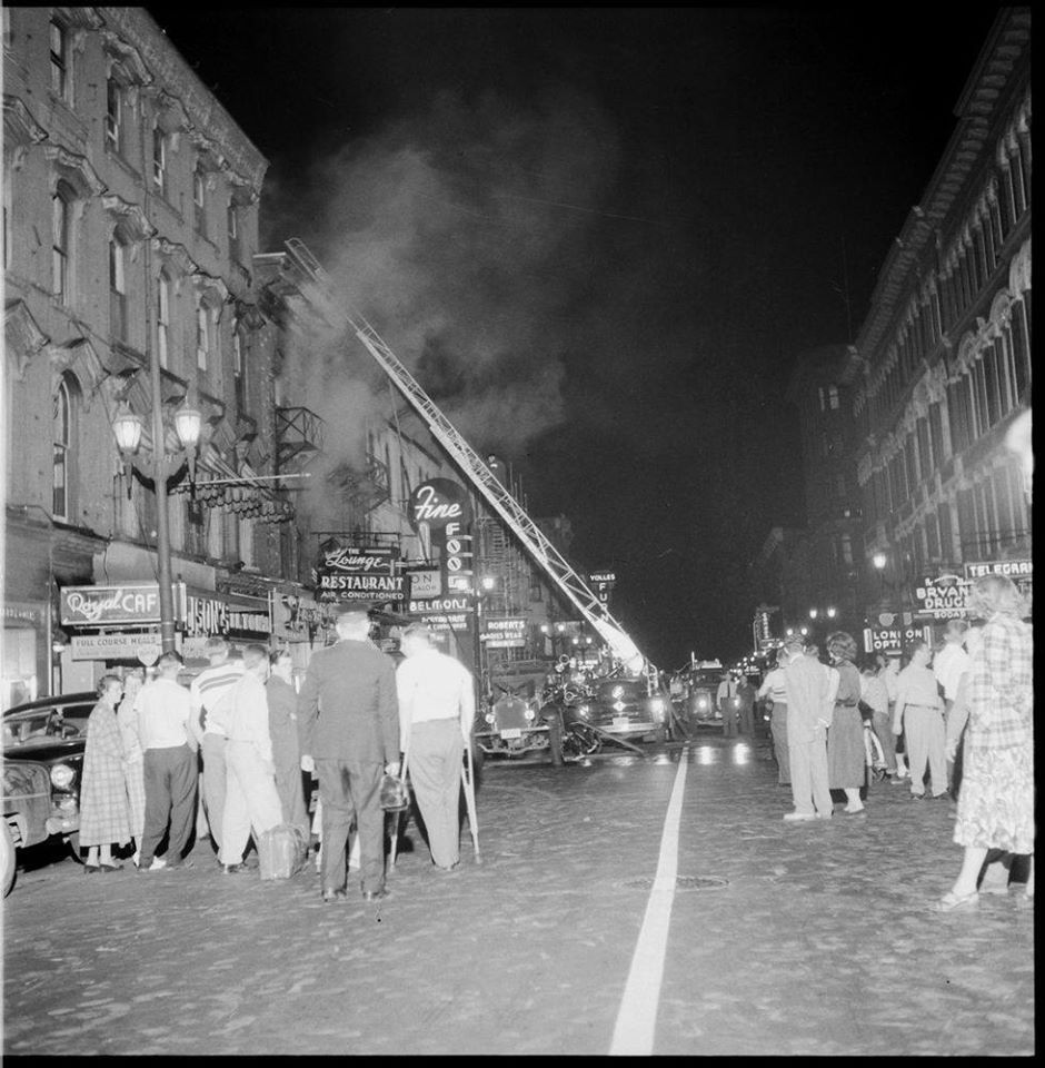 People gathering the street to watch the ladder truck extended up in to the building building