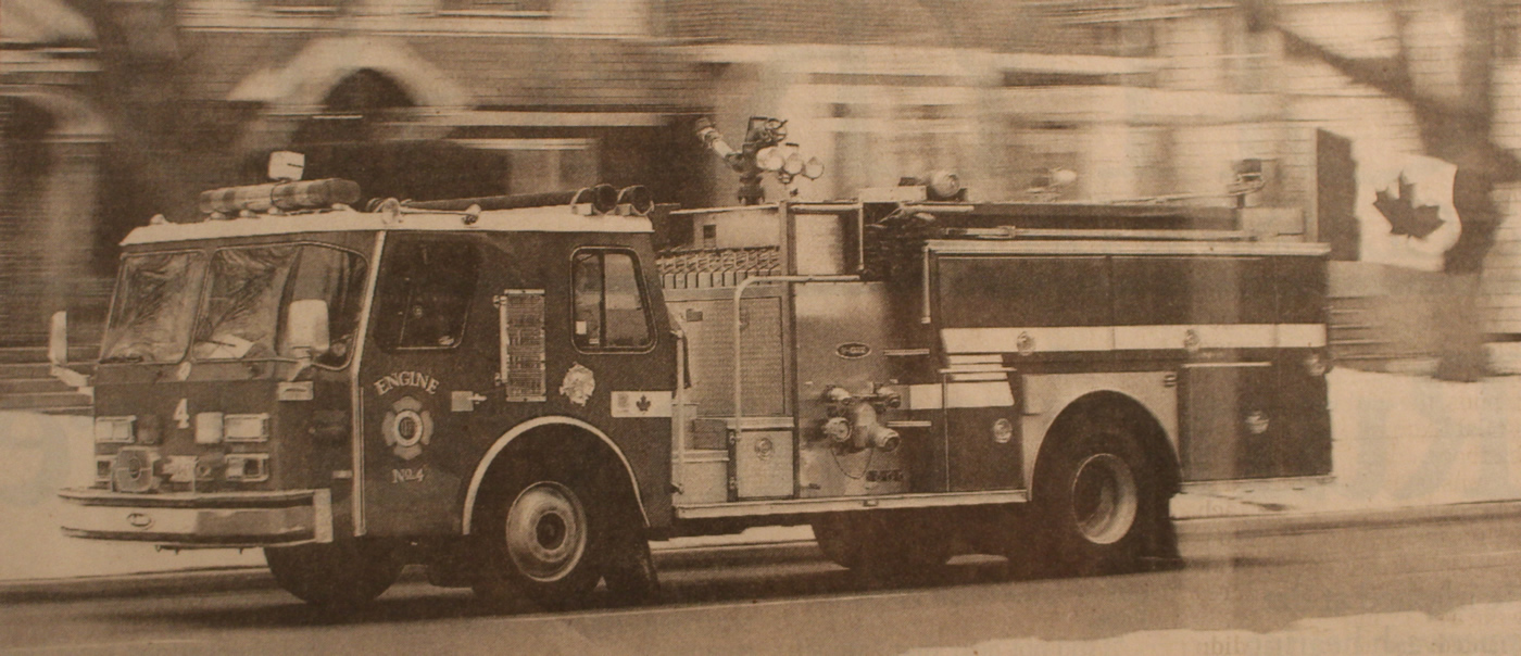 Engine 4 driving down the road with a Canadian flag on display on the back of the truck.