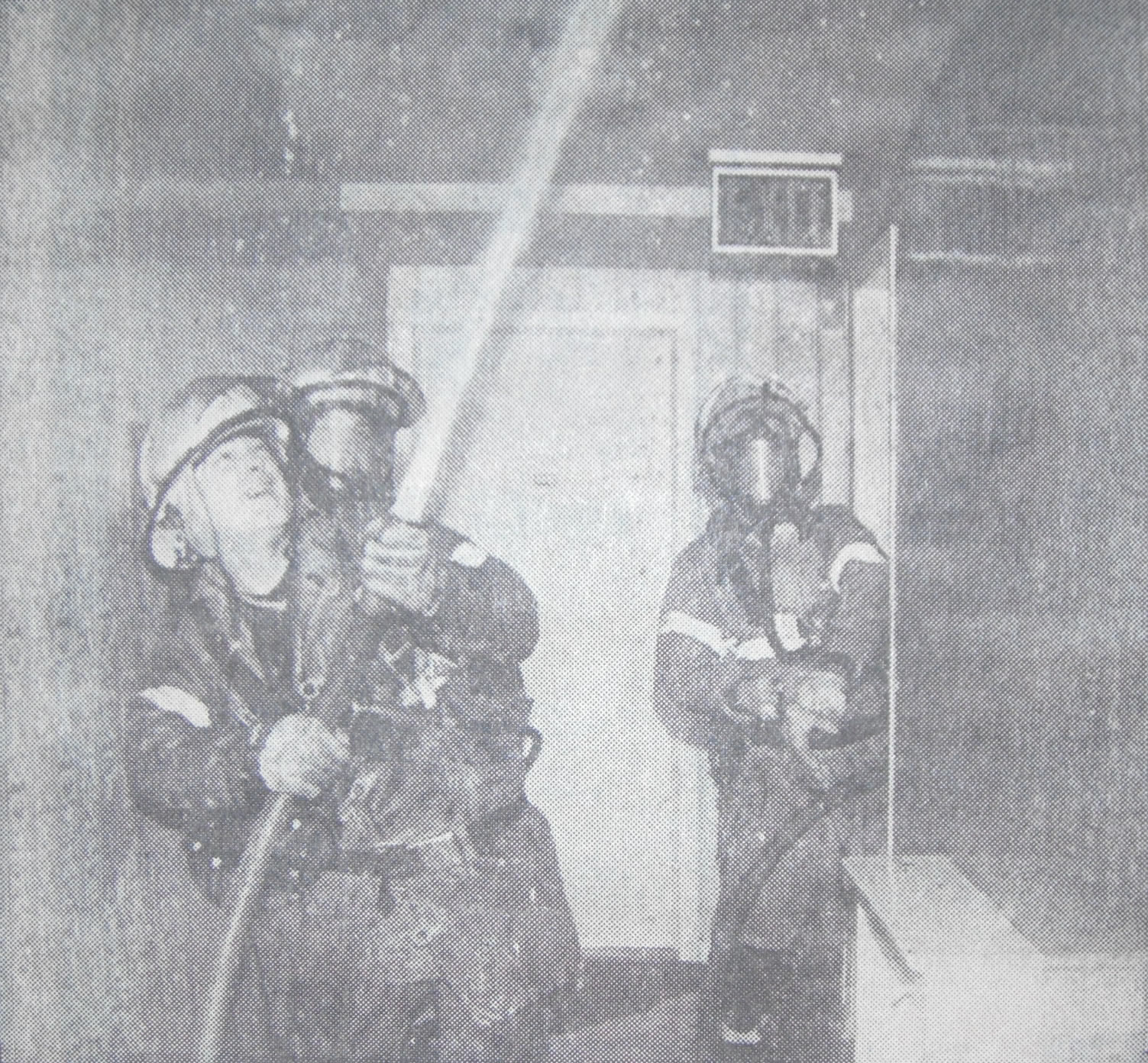 Fire fighters spraying water during an interior fire overhauling operation.