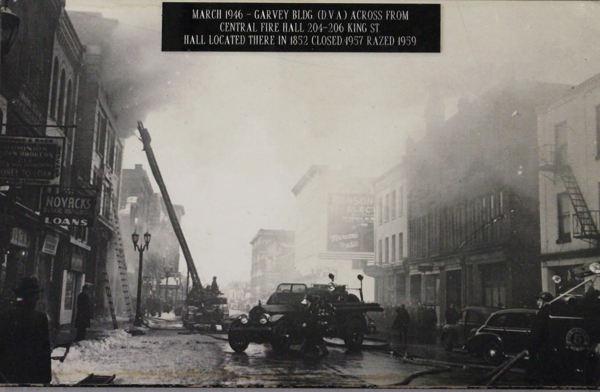 Large ladder with fire fighter spraying water into a fourth floor window