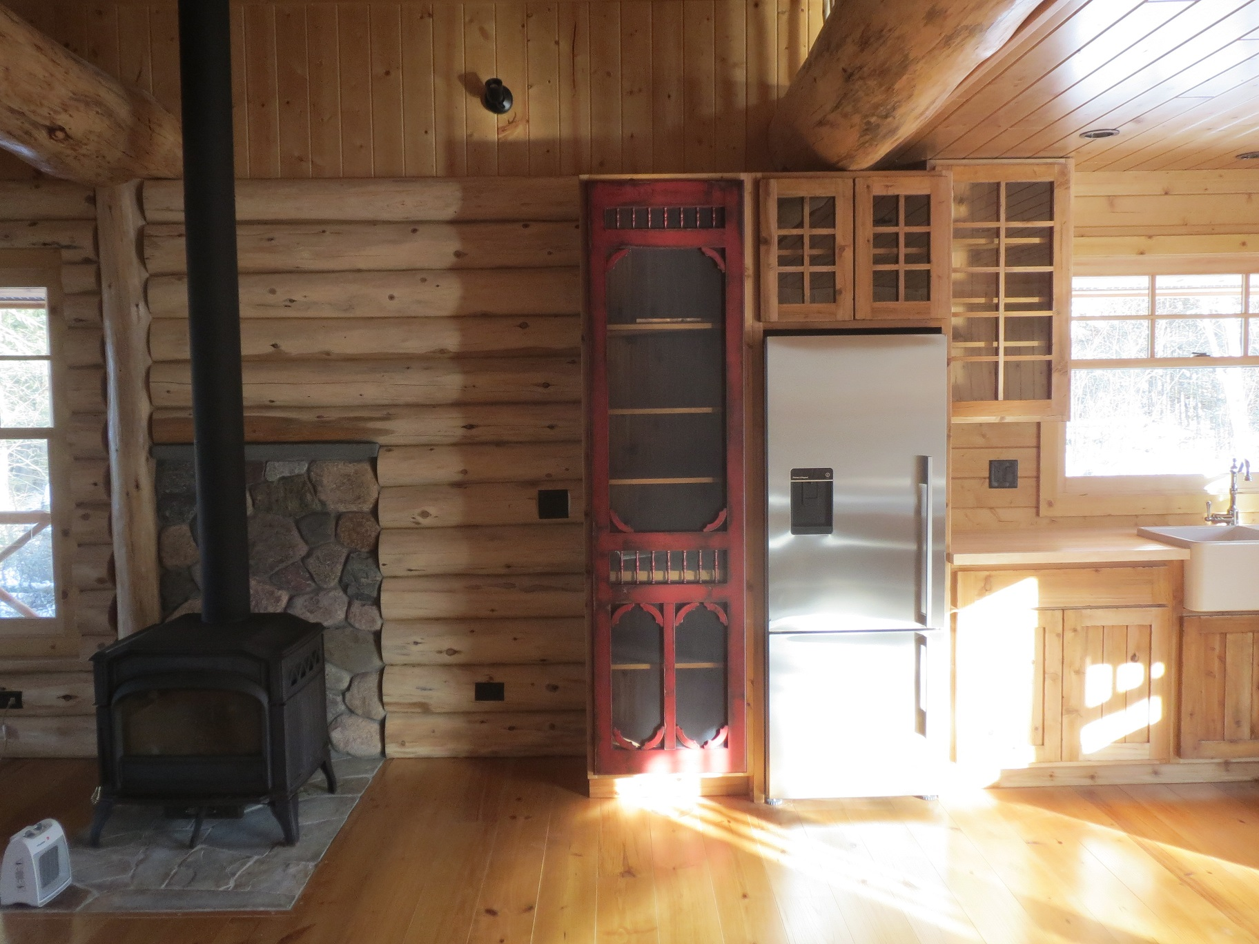 Red screen door on cabinets next to the wood stove in the living room