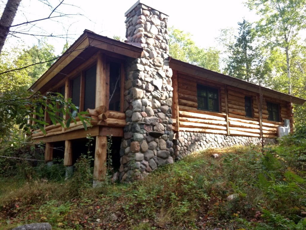 Rustic Stone chimney on log cabin