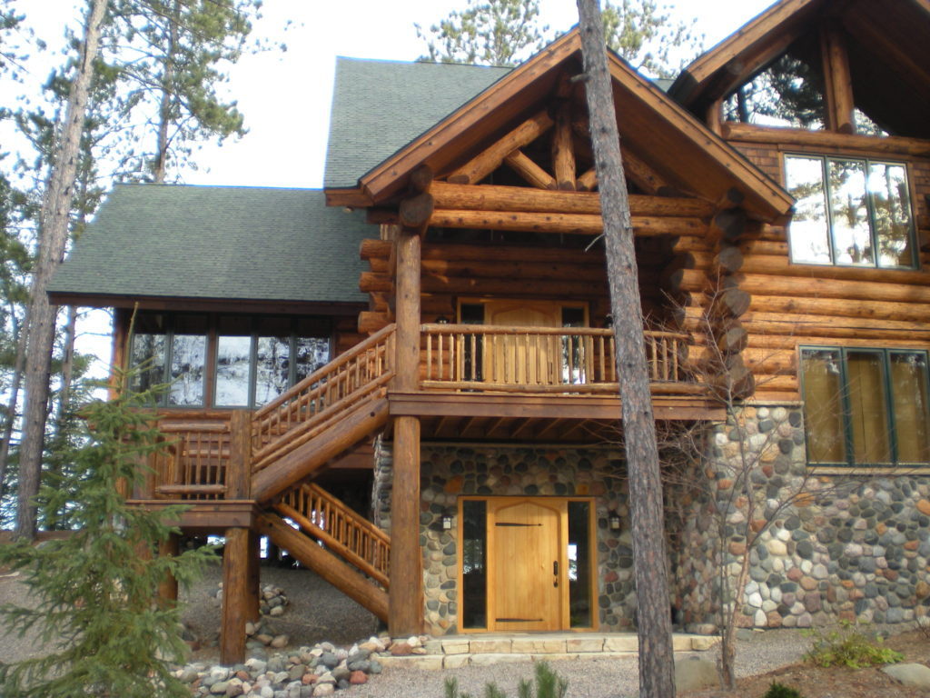 Large cedar and stone log home entry view