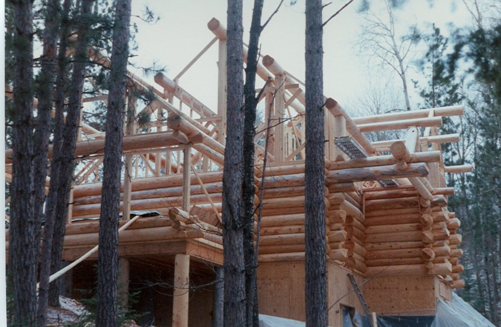 Log construction in progress, roof log system