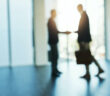 Defocused shot of two businessmen shaking hands in an office