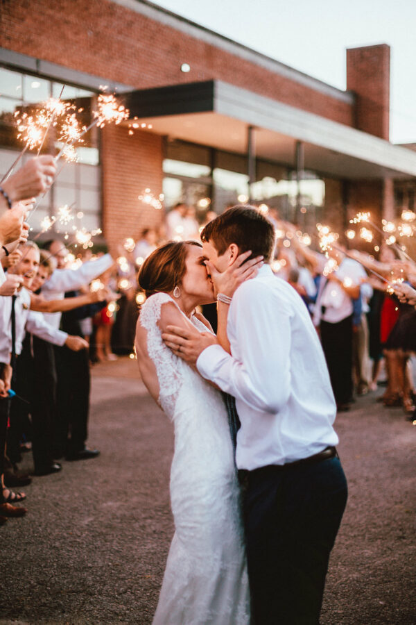 A kiss outside among friends and sparklers.