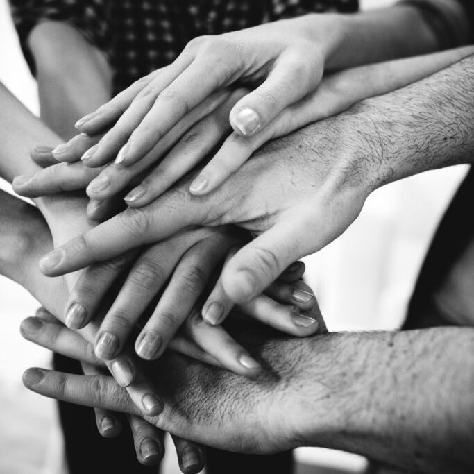 Black and white photo of people putting their hands together. Group of people. Shot from above.