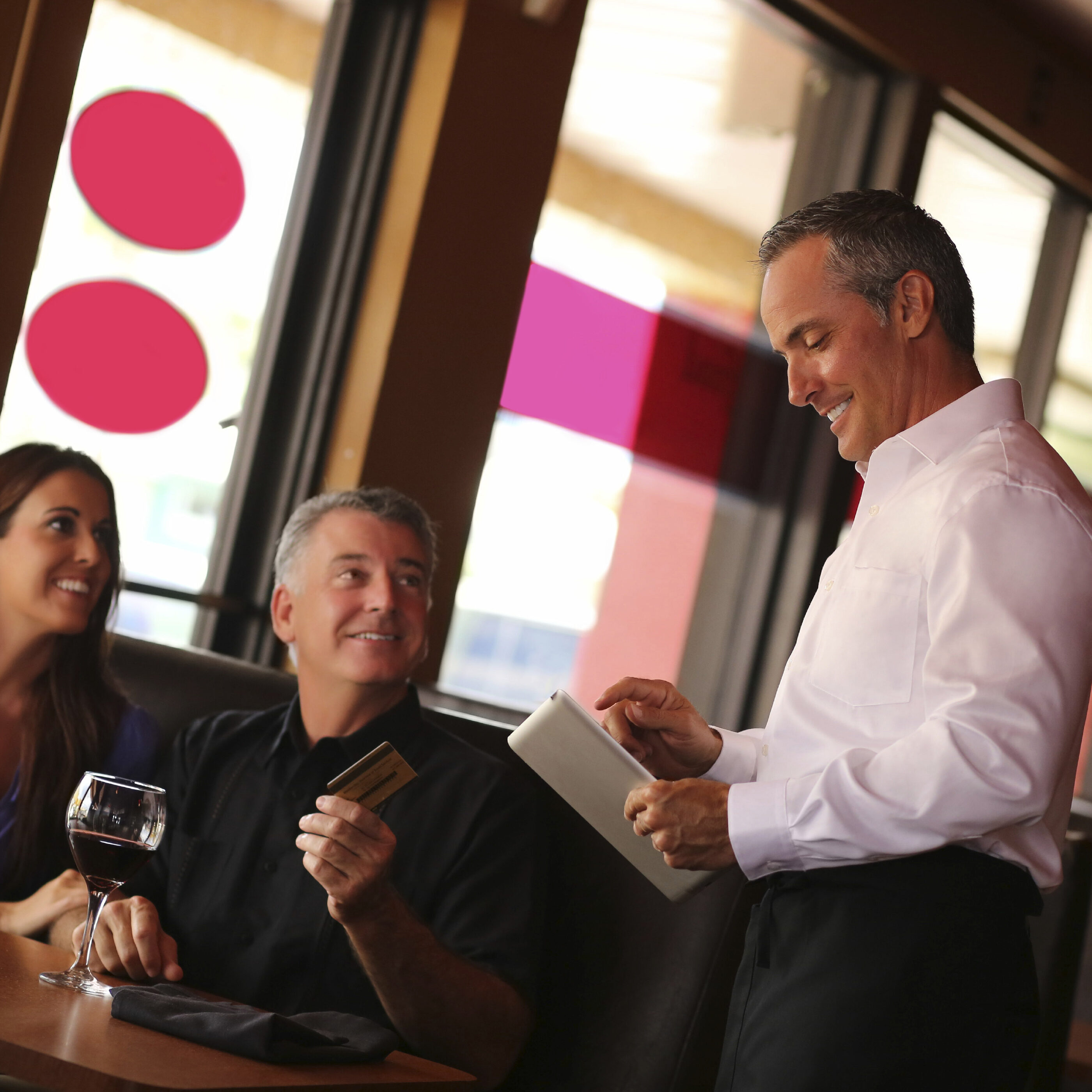 Happy mature couple holding credit card while waiter using digital tablet in restaurant