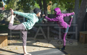Two Women Holding Hands Standing On One Foot Each Doing Yoga