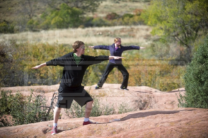 Man and Woman Standing On Rock Outstretching Arms Doing Yoga
